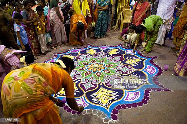 Women creating rangoli (decorative motif) with coloured powder at entrance to Sri Meenakshi Temple in preparation for festival procession.