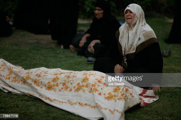 A women cries over the dead body of a relative as US Army soldiers of the DCO 2/325 AIR 82nd Airborne Division investigate the shooting while they...