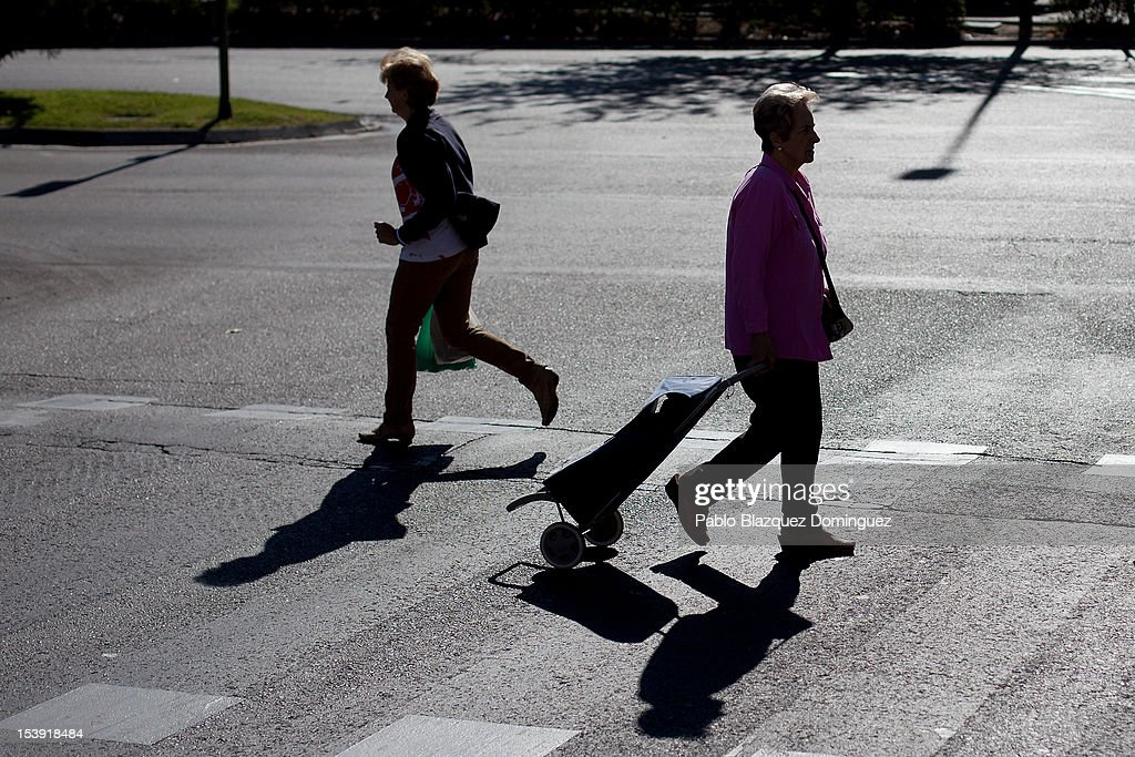 Women cross the road with their shopping in a street market on October 11, 2012 in Madrid, Spain. Ratings agency Standard & Poor's has cut Spain's credit rating from BBB+ down to BBB-. The Spanish government has already introduced spending cuts and tax rises in an attempt to ease their debt and reduce their high unemployment levels. Spanish Economy Minister Luis de Guindos maintains that his country will not need to ask for a bailout.