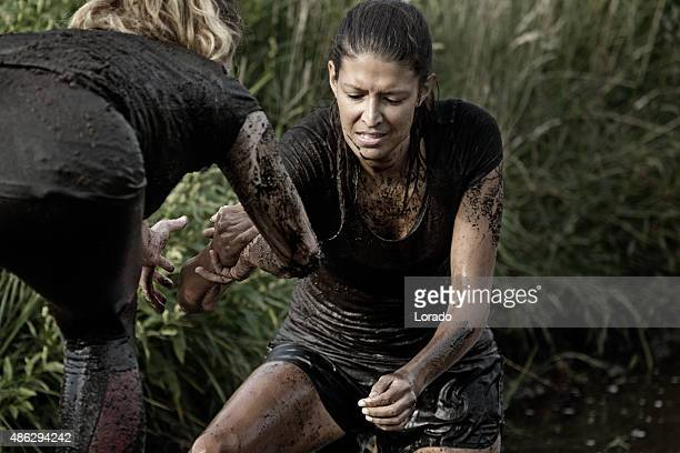 women crossing mud obstacle
