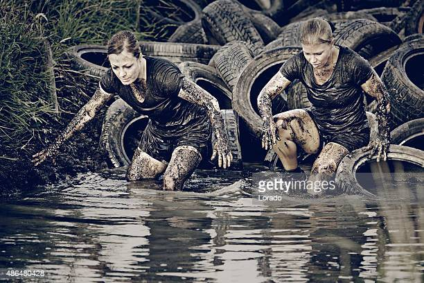 women crossing muddy canal with tires