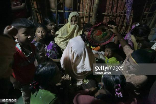 COX'S BAZAR BANGLADESH NOVEMBER 30 Women crowd around Nur Begum who doesn't know her age but thinks she is between 14 and 16 years old on the day of...