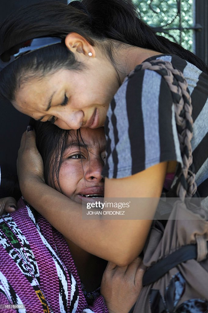 Women cry after recognizing the body of a relative at a crime scene next to a van in downtown Guatemala City on Febrary 9, 2013. The vehicle was attacked by unidentified gunmen while traveling toward a prison; leaving two prison guards and a woman dead, authorities stated. AFP PHOTO/Johan ORDONEZ