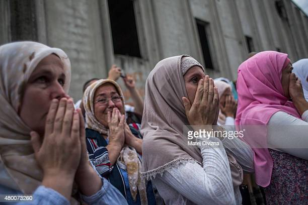Women cry near a truck carrying 136 coffins of victims of the 1995 Srebrenica massacre in front of the hall at the Potocari cemetery and memorial...