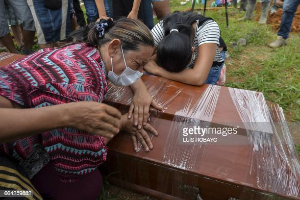 TOPSHOT Women cry over the coffin of a relative killed by a mudslide caused by heavy rains at the cemetery in Mocoa Putumayo department Colombia on...