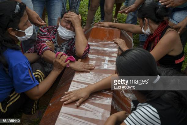 Women cry over the coffin of a relative killed in the mudslides caused by heavy rains at the cemetery in Mocoa Putumayo department Colombia on April...