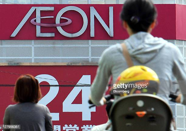 Women cycle in front of an Aeon Co supermarket in Tokyo Japan on Tuesday Oct 4 2011 Aeon Co Japan's biggest supermarket operator is expected to...