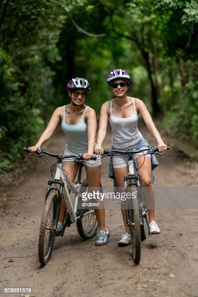 Women cycling outdoors and looking very happy