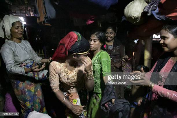 COX'S BAZAR BANGLADESH NOVEMBER 30 Women dance around Nur Begum who doesn't know her age but thinks she is between 14 and 16 years old on the day of...
