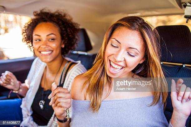 Women dancing together in car