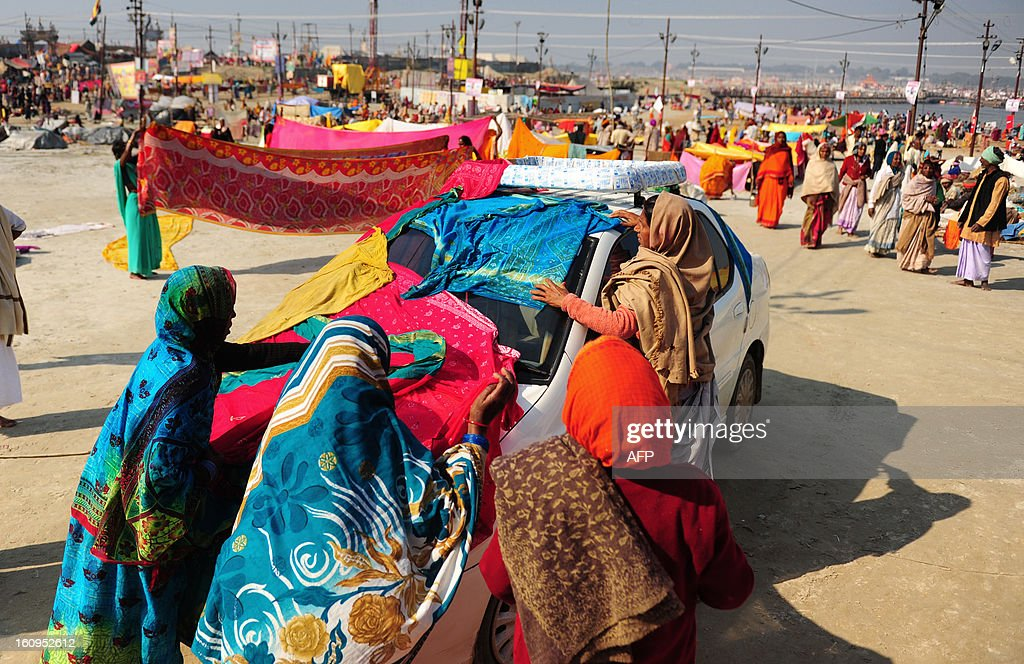 Women devotees dry their saris on a car after taking a dip at Sangam or the confluence of the Yamuna, Ganges and mythical Saraswati rivers in the early morning during the Kumbh Mela festival in Allahabad February 8, 2013. The Kumbh Mela will see up to 100 million worshippers gather over 55 days to take a ritual bath in the holy waters, believed to cleanse sins and bestow blessings.