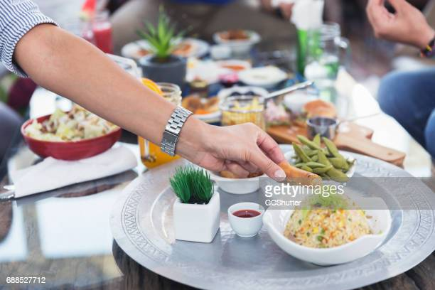 Women dipping spring rolls into sauce