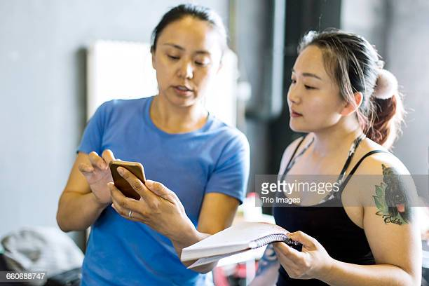 women discuss with mobile phone in gym