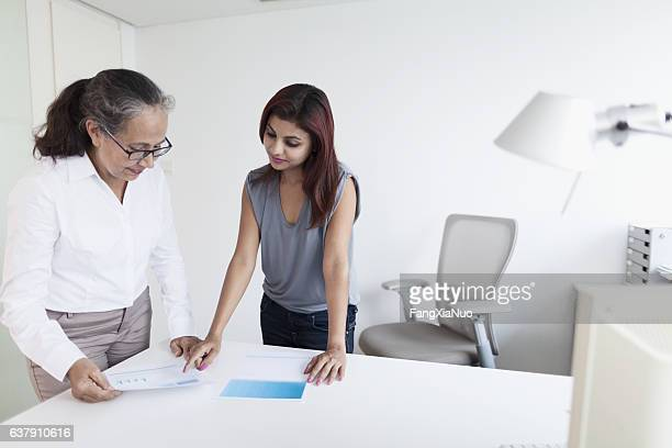 Women discussing document in office together