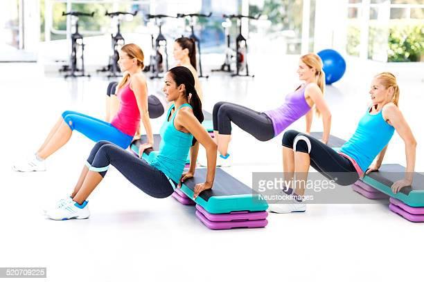Femmes faisant de l'aérobic avec étapes dans la salle de sport