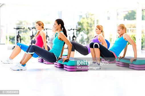 Women Doing Aerobics Using Steps In Health Club