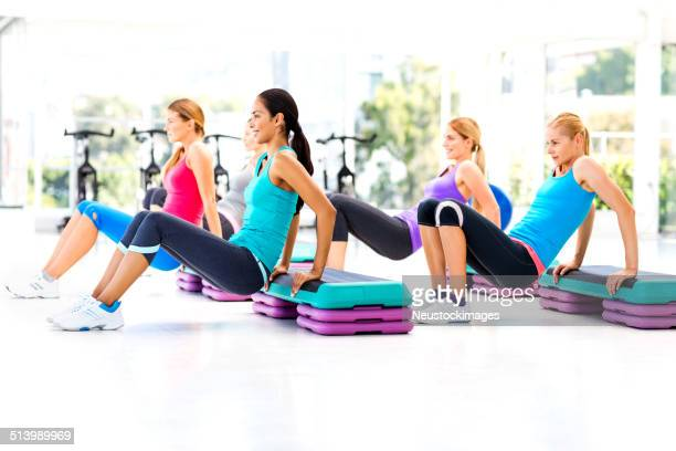 Women Doing Aerobics Using Steps In Health Club