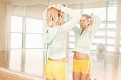 Women doing her hair in mirror in gymnasium
