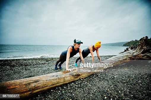 Women doing push ups on log on beach
