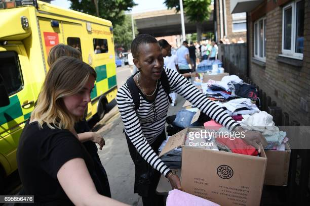Women donate clothes to a stall which has been set up to help people near the burning 24 storey residential Grenfell Tower block in Latimer Road West...