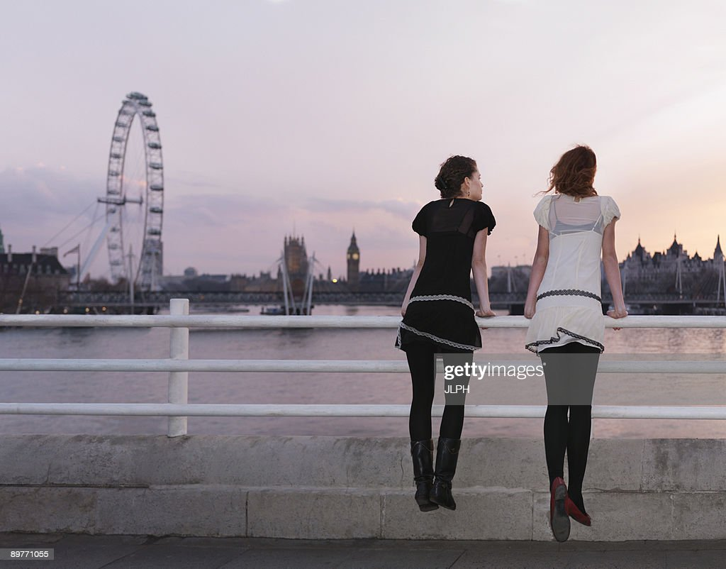 Women drawing on balustrade at sunset : Stock Photo