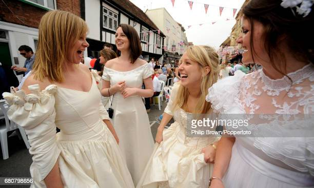 Women dressed as brides laugh during a street party in Eton High Street near Windsor Castle on the day that Kate Middleton married Britains Prince...