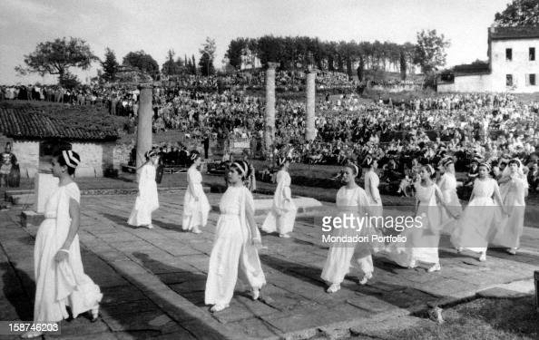 Women dressed as vestals dancing on the forum of Velleia around the altar Lugagnano Val d'Arda 1960s