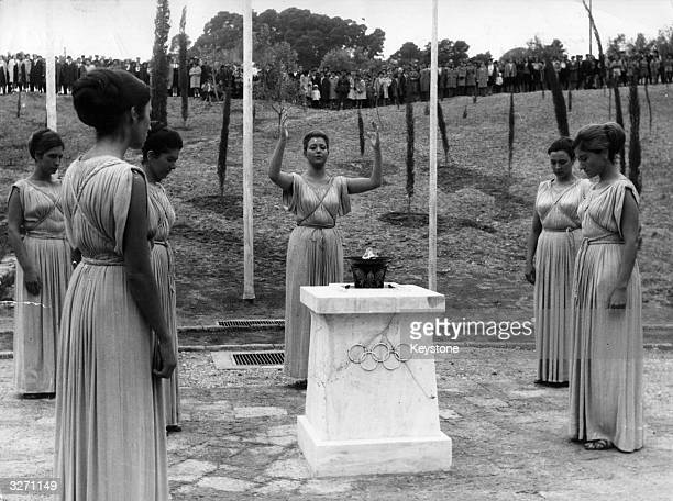 Women dressed in ancient Greek tunics at Olympia performing the ceremony of lighting the Olympic Flame at the sacred altar After the ceremony the...