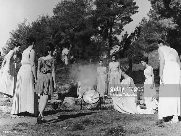 Women dressed in ancient Greek tunics use the sun's rays to light the Olympic Flame at the ancient Greek city of Olympia 1976 After the ceremony the...