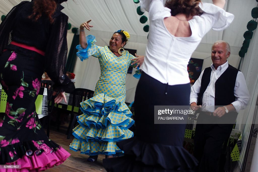 Women dressed in 'flamenca' costume dance 'sevillanas' as they participate in the 'Feria de Abril' (April Fair) in Barcelona, on April 30, 2016. This fair is one of the most important outside Andalusia due to the large number of descendants of Andalusian emigrants living in Catalonia and it hosts more than one million visitors in ten days. / AFP / PAU