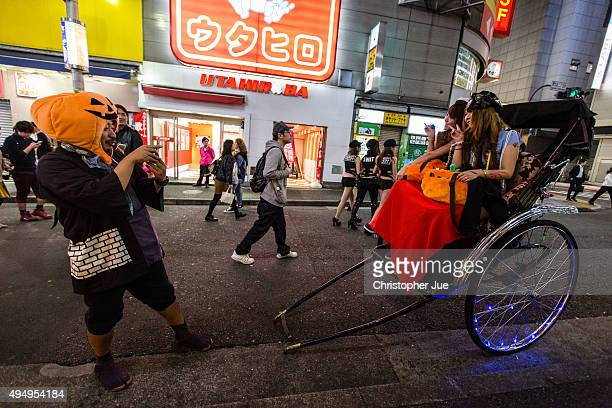 Women dressed in Halloween costumes pose for a photo on a rickshaw during a gathering in Tokyo's Shibuya district on October 30 2015 in Tokyo Japan...