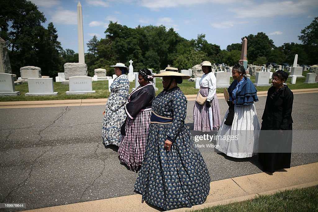 Women dressed in period clothing attend an event at the gravesite of Buffalo Soldier Col. Charles Young, at Arlington Cemetery, June 5, 2013 in Arlington, Virginia. The event was hosted by the National Coalition of Black Veterans and the Omega Psi Phi Fraternity to celebrate the 90th anniversary of 'Buffalo Soldier' and military leader Col. Charles Young's internment in Arlington Cemetery.