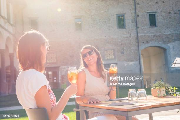 Women drinking cocktails outdoor, Italy
