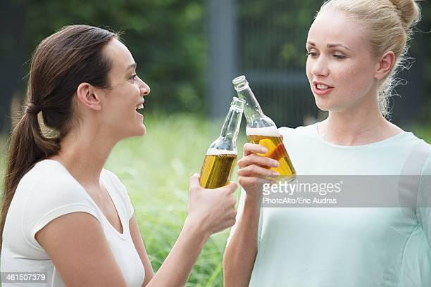Women drinking together, clinking bottles