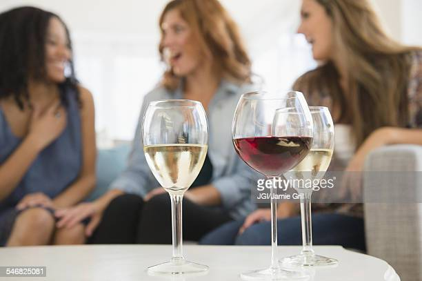 Women drinking wine and talking on sofa in living room