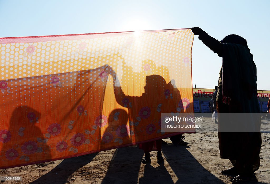 Women dry wet saris in the sun and wind after bathing in the confluence of the Yamuna and Ganges river during the Maha Kumbh Mela festival in Allahabad on February 8, 2013. The Kumbh Mela in the town of Allahabad will see up to 100 million worshippers gather over 55 days to take a ritual bath in the holy waters, believed to cleanse sins and bestow blessings.