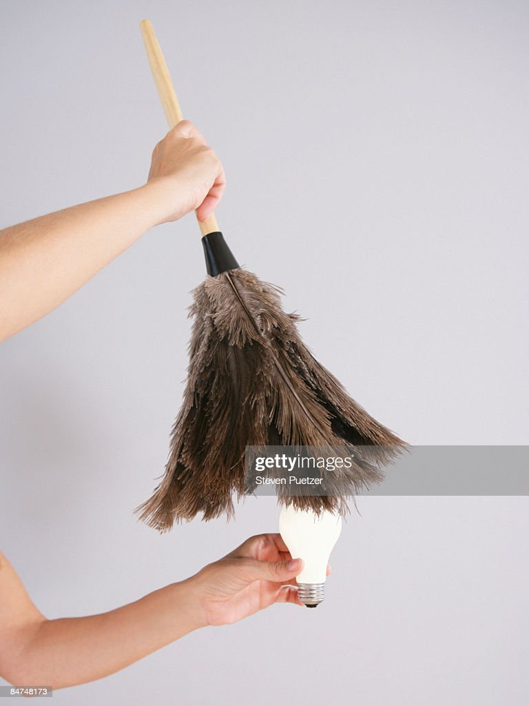 Women dusting off lightbulb with feather duster : Stock Photo