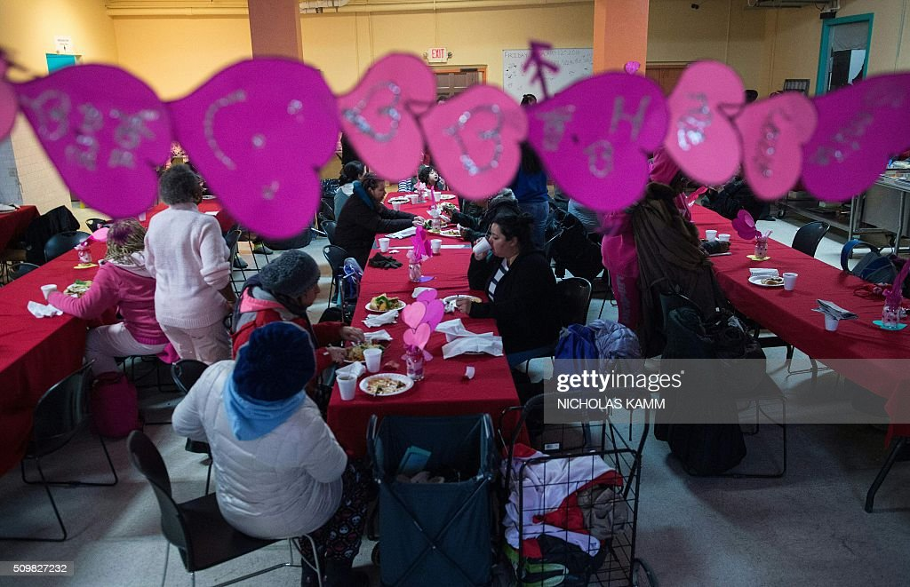 Women eat a meal during a Spa Day for homeless and at-risk women organized by ThriveDC, an organization fighting homelessness, in Washington, DC, on February 12, 2016. Recent research published in the American Journal of American Health finds that unstably-housed women experience dramatically higher incidence of physical, sexual and emotional violence. / AFP / Nicholas Kamm