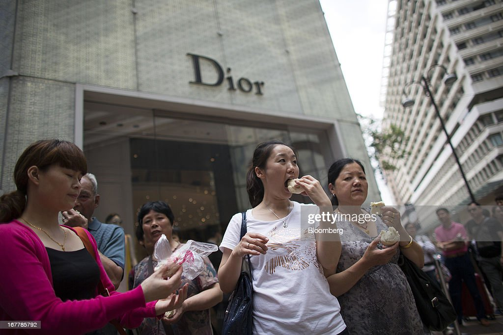 Women eat bread in front of a Christian Dior SA store in the Tsim Sha Tsui area of Hong Kong, China, on Tuesday, April 30, 2013. Financial Secretary John Tsang on Feb. 27 projected annual growth of 1.5 percent to 3.5 percent this year following 2012's 1.4 percent, the weakest rate since 2009 as Europe's sovereign debt crisis sapped global demand. Photographer: Lam Yik Fei/Bloomberg via Getty Images