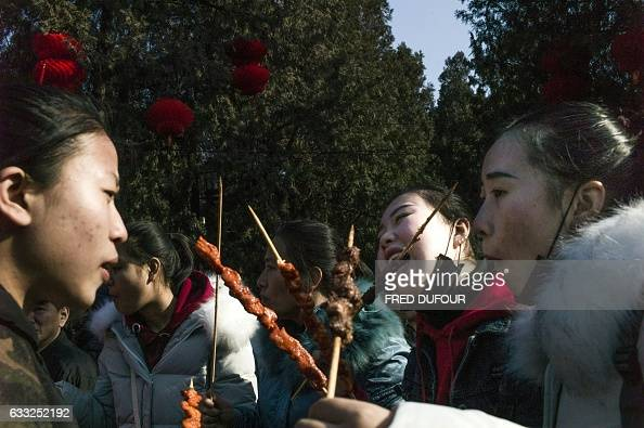 Women eat snacks at a temple fair in Ditan park during Lunar New Year celebrations in Beijing on February 1 2017 The Lunar New Year fell on January...