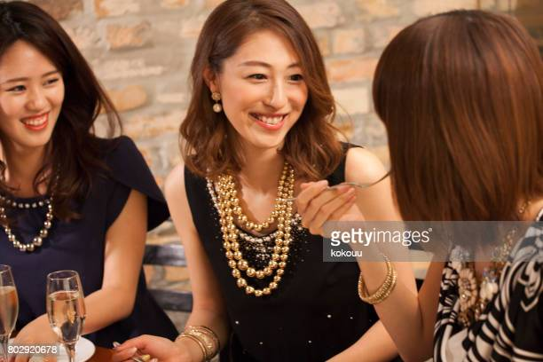 Women eat while having a happy conversation.