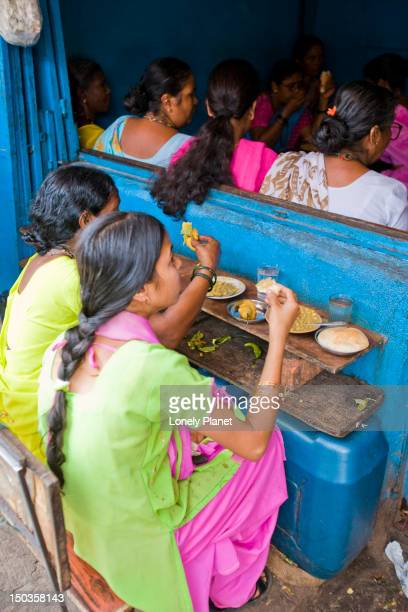 Women eating bhaji pau and chilli fritters at Mapusa Market.