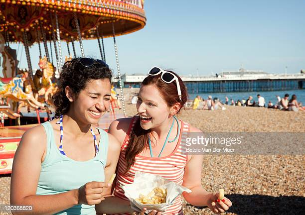 Women eating fish and chips  on beach.
