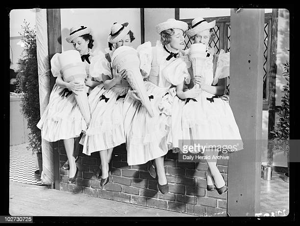 Women 'eating' giant ice cream cones 1936 A photograph of four women in milkmaid costumes pretending to eat giant ice cream cones taken by Tomlin for...