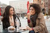 Women eating together at sidewalk cafe