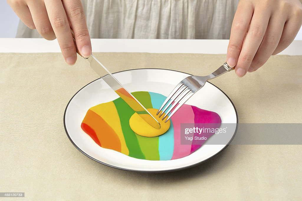 Women eating with a fork and knife colorful egg : Stock Photo