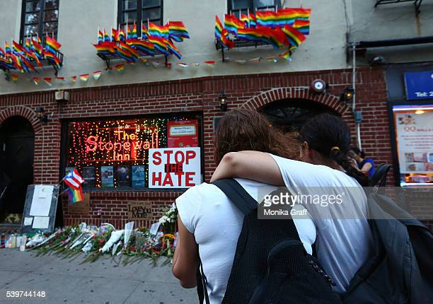 Women embrace before a makeshift memorial in front of the Stonewall Inn where a vigil was held following the massacre that occurred at a gay Orlando...
