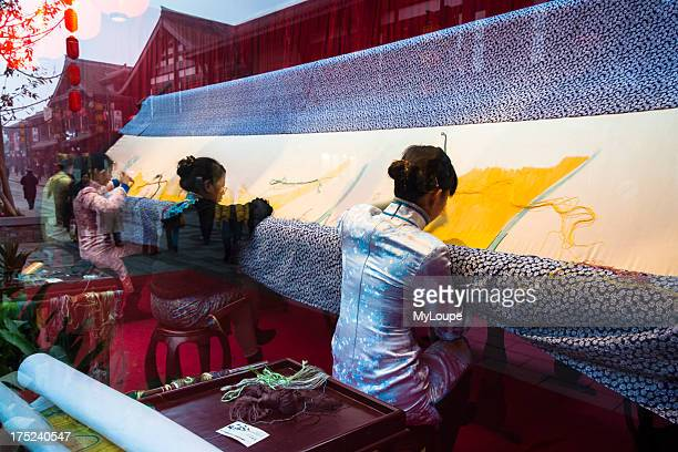 Women embroidering a big tapestry behind a glass window shop in Chengdu China