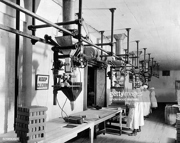 Women employees using Scott filling machines in a factory circa 1913