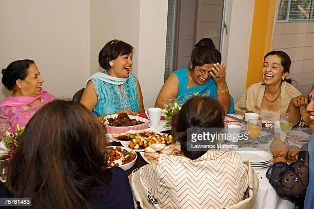 Women Enjoying a Laugh During Dinner